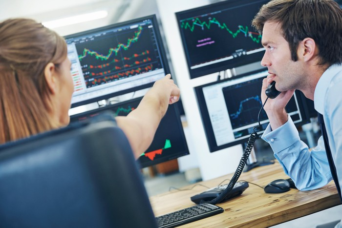 Two professional traders looking at computer monitors featuring charts and investing data.